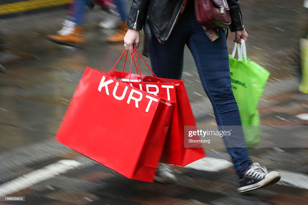 A pedestrian carries Kurt Geiger-branded shopping bags in the Covent Garden district of London U.K., on Monday, Dec. 31, 2012. The number of Britons making shopping trips for post-holiday bargains barely increased on the day after Christmas as more people sought discounts online. Photographer: Jason Alden/Bloomberg via Getty Images