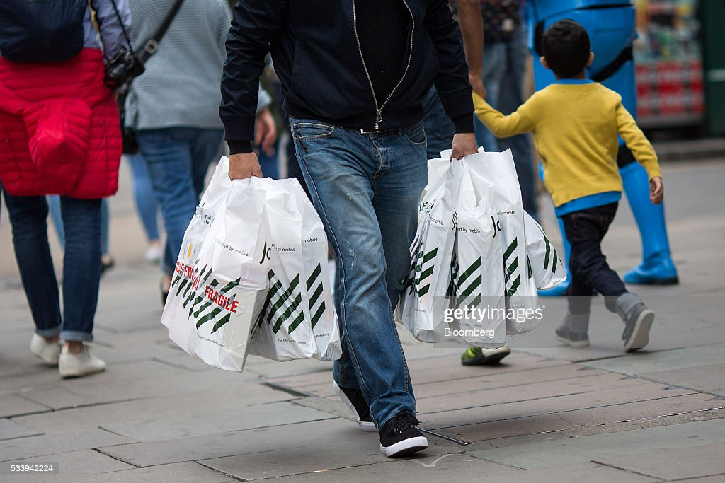 A pedestrian carries multiple John Lewis Plc branded shopping bags along Oxford Street in London, U.K., on Tuesday, May 24, 2016. U.K. retail sales began the second quarter with more momentum than economists forecast. Photographer: Simon Dawson/Bloomberg via Getty Images