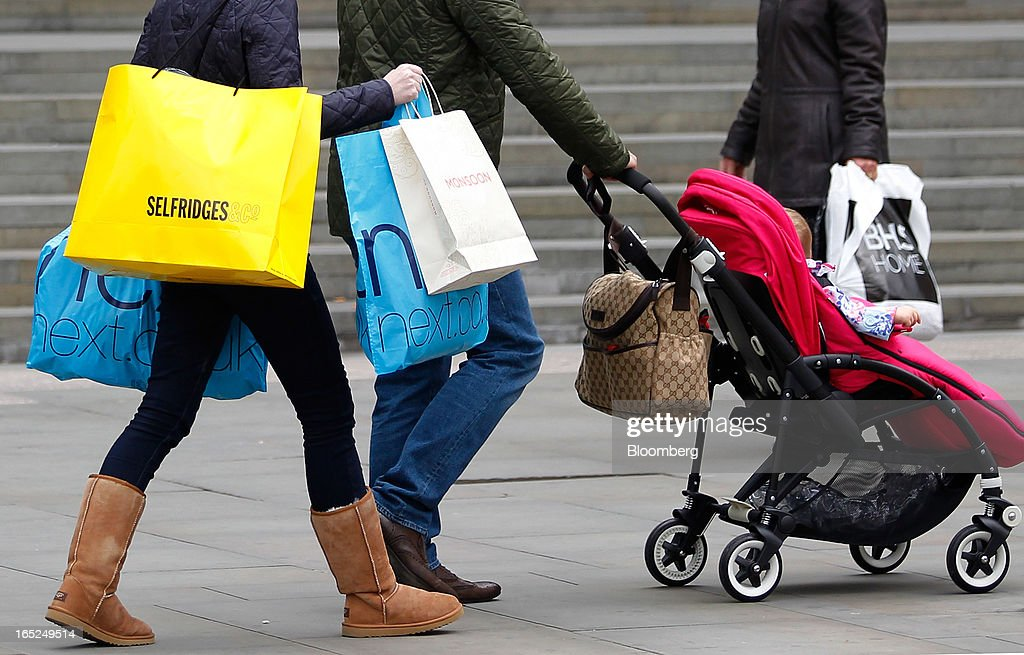 A pedestrian carries Selfridges & Co. and Next Plc-branded shopping bags along a street in Manchester, U.K., on Monday, April 1, 2013. U.K. retail sales unexpectedly stagnated in March in a sign that consumer spending remains under pressure from higher energy bills and weak wage growth. Photographer: Paul Thomas/Bloomberg via Getty Images