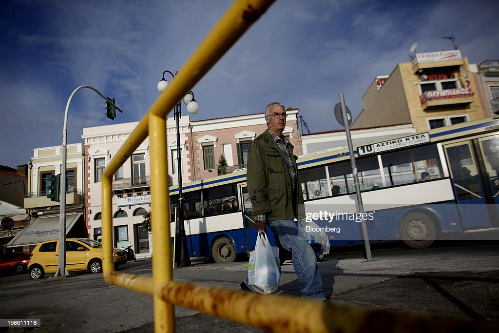 A pedestrian carries shopping bags along the harbor front in Mytilene, on the island of Lesbos, Greece, on Saturday, Dec. 8, 2012. In recent months, Lesbos has become a hot spot for migrants as Greece struggles to cope with waves of refugees from Middle Eastern conflict even as it reels from economic crisis at home. Photographer: Kostas Tsironis/Bloomberg via Getty Images