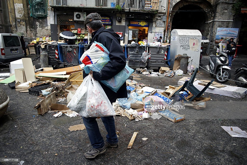 A pedestrian carries shopping bags as he passes a pile of garbage strewn around trash cans outside a store in Naples, Italy, on Saturday, Feb. 1, 2014. In Naples, the local youth unemployment rate in 2012 was 53.6 percent compared to a national average of 35.3 percent. Photographer: Alessia Pierdomenico/Bloomberg via Getty Images