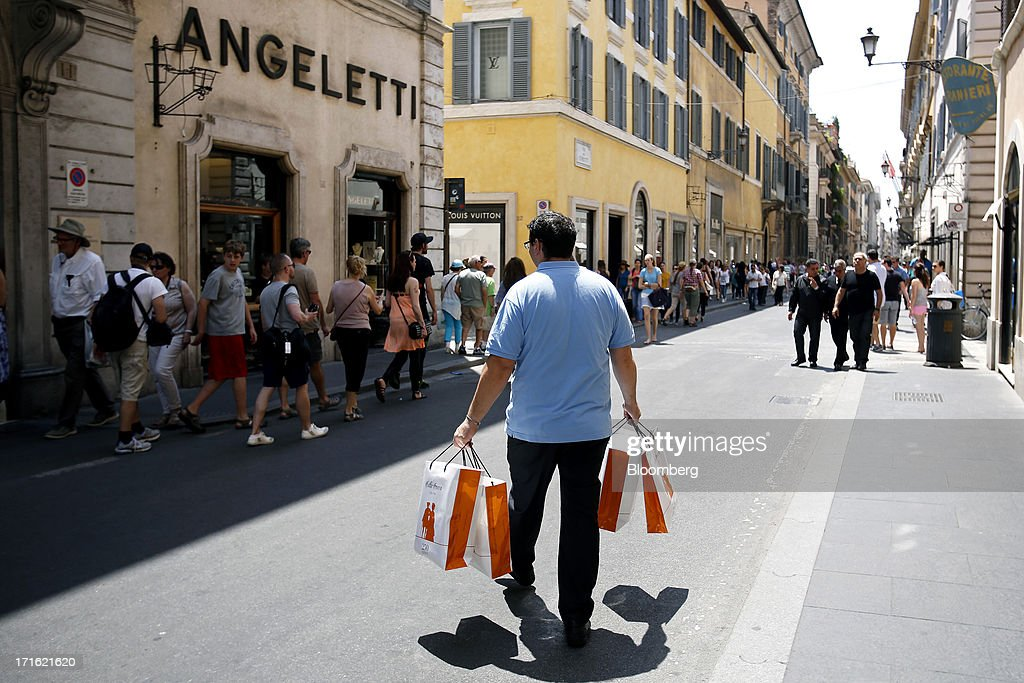 A pedestrian carries shopping bags as he passes stores on Via Condotti in Rome, Italy, on Wednesday, June 26, 2013. Italian household confidence rose this month as consumers grew optimistic about the country's outlook as Prime Minister Enrico Letta's government plans to cut taxes and boost youth employment. Photographer: Alessia Pierdomenico/Bloomberg via Getty Images