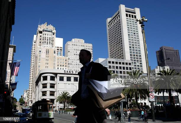 A pedestrian carries shopping bags as he walks through Union Square on February 22 2011 in San Francisco California The Conference Board's consumer...