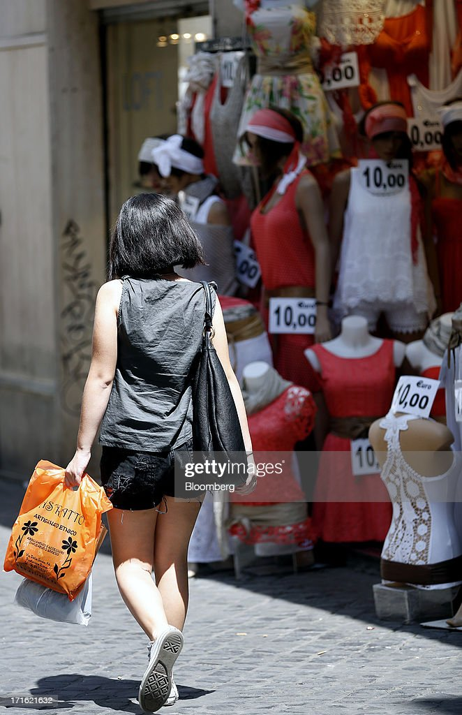A pedestrian carries shopping bags as she passes a discount clothes store in Rome, Italy, on Wednesday, June 26, 2013. Italian household confidence rose this month as consumers grew optimistic about the country's outlook as Prime Minister Enrico Letta's government plans to cut taxes and boost youth employment. Photographer: Alessia Pierdomenico/Bloomberg via Getty Images
