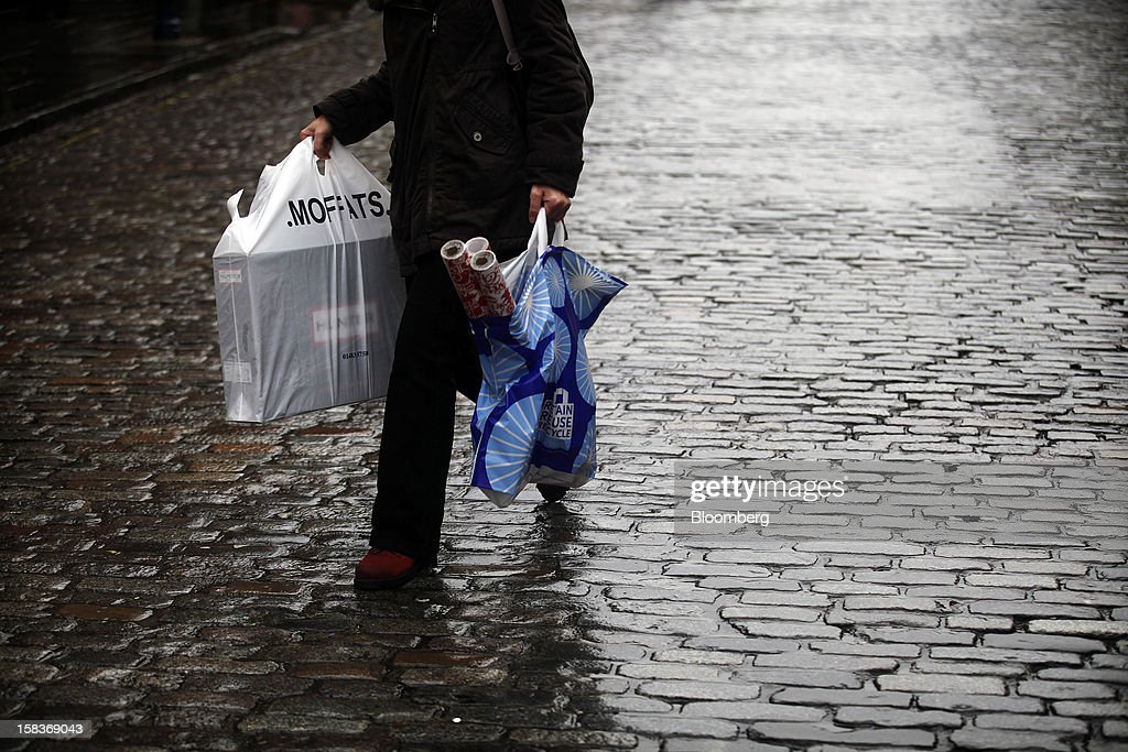 A pedestrian carries shopping bags as she walks over rain-covered cobblestones in Guildford, U.K., on Friday, Dec. 14, 2012. Standard & Poor's lowered its outlook on Britain's top credit rating to negative, citing weak economic growth and a worsening debt profile. Photographer: Simon Dawson/Bloomberg via Getty Images