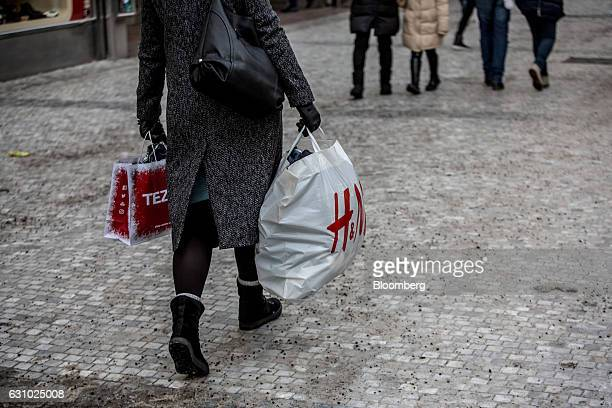 A pedestrian carries shopping bags branded with Hennes Mauritz AB and Tezenis along a retail street in central Prague Czech Republic on Thursday Jan...