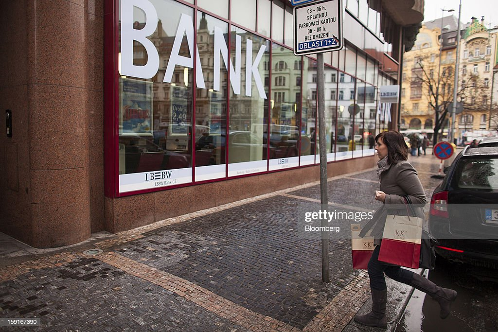 A pedestrian carries shopping bags past a Landesbank Baden-Wuerttemberg, or LBBW, bank branch in Prague, Czech Republic, on Tuesday, Jan. 8, 2013. The Czech economy is showing weak domestic demand as households and businesses cut spending due to government austerity programs and the euro area's debt crisis. Photographer: Bartek Sadowski/Bloomberg via Getty Images
