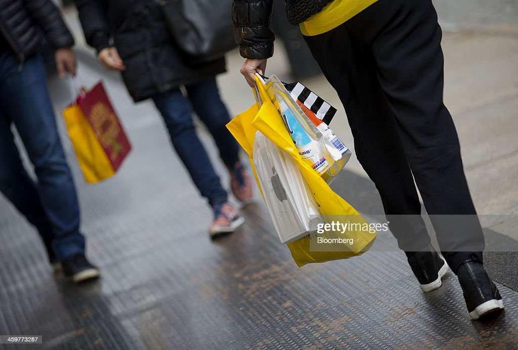 A pedestrian carries shopping bags while walking in the Soho neighborhood of New York, U.S., on Monday, Dec. 30, 2013. The failure of United Parcel Service Inc. (UPS) and FedEx Corp. to deliver packages in time for Christmas has exposed the perils of retailers promising to get last-minute gifts to customers. Photographer: Jin Lee/Bloomberg via Getty Images