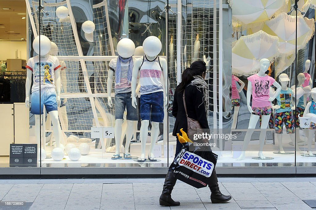 A pedestrian carrying a Sports Direct.com shopping bag walks past a widow display at the C&A store, operated by the C&A Group in Brussels, Belgium, on Monday, May 13, 2013. Euro-area data this week will probably reveal economic scars of the sovereign debt crisis confirming that the region is now suffering the longest recession since the single currency's creation. Photographer: Jock Fistick/Bloomberg via Getty Images