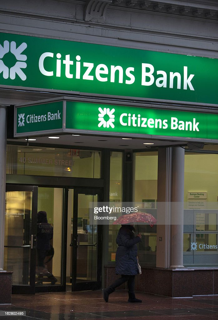 A pedestrian carrying an umbrella passes in front of a Citizens Financial Group Inc. bank branch in Boston, Massachusetts, U.S., on Wednesday, Feb. 27, 2013. Royal Bank of Scotland Group Plc will this week announce plans to sell a stake in Citizens Financial Group Inc. and shrink assets at its investment-bank by as much as 30 billion pounds, said a person with knowledge of the plans, who asked not to be identified because the matter is private. Photographer: Kelvin Ma/Bloomberg via Getty Images