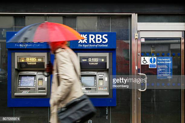 A pedestrian carrying an umbrella to shelter from the rain passes automated teller machines outside a closed Royal Bank of Scotland Group Plc bank...