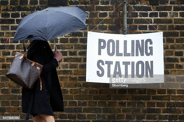 A pedestrian carrying an umbrella to shelter from the rain walks past a sign for a polling station in the European Union referendum hanging on a wall...