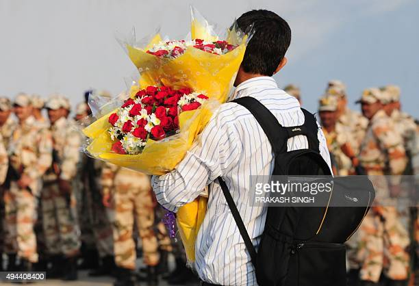 A pedestrian carrying floral bouquets walks past Indian security personnel wait to be deployed during The IndiaAfrica Summit at The Indira Gandhi...