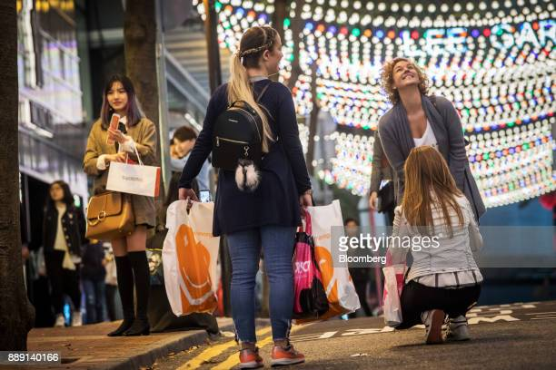 A pedestrian carrying shopping bags pose for photographs under illuminated Christmas lights in Hong Kong China on Saturday Dec 9 2017 With more...