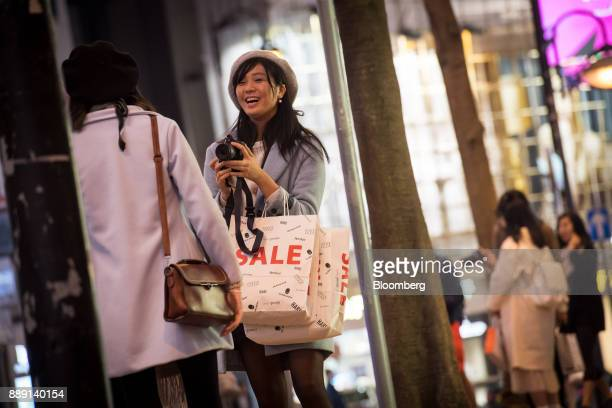 A pedestrian carrying shopping bags take photographs in Hong Kong China on Saturday Dec 9 2017 With more Chinese tourists likely to travel to Hong...