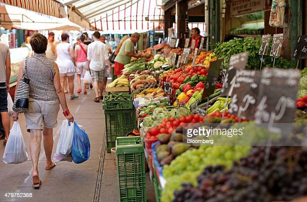 A pedestrian carrying shopping bags walks past fruits and vegetables for sale on a market stall at Naschmarkt in Vienna Austria on Friday July 3 2015...