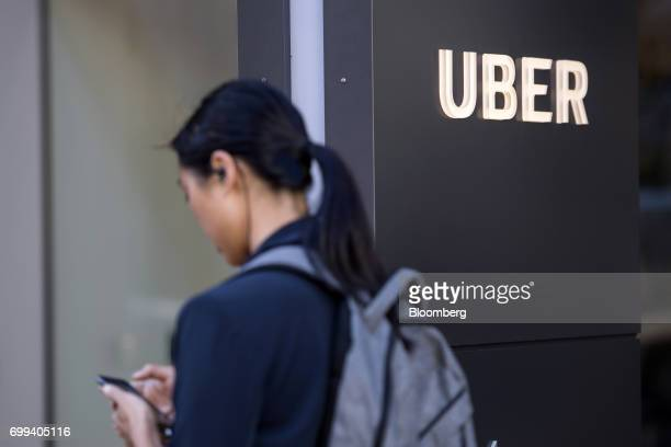A pedestrian checks a mobile device in front of the Uber Technologies Inc headquarters building in San Francisco California US on Wednesday June 21...