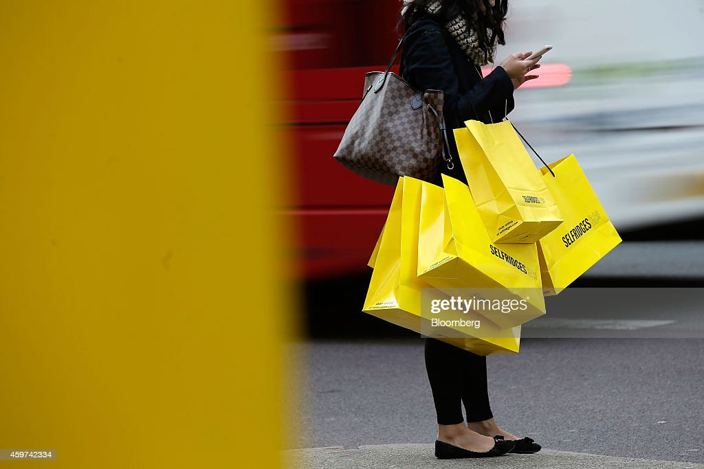 A pedestrian checks her mobile phone device as she carries branded shopping bags from Selfridges on Oxford Street in London UK on Saturday Nov 29...