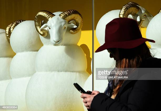 A pedestrian checks her mobile phone in front of next year's 'Year of the Sheep' part of a display window at a department store in the Ginza shopping...