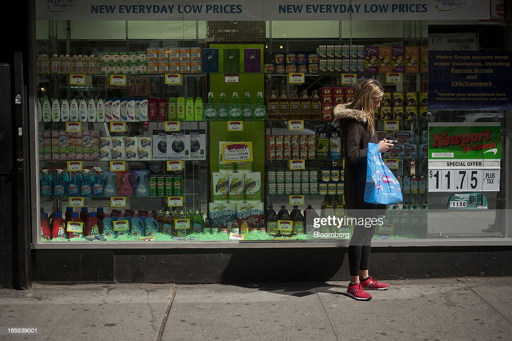 A pedestrian checks her phone while carrying a shopping bag in New York, U.S., on Thursday, April 4, 2013. Confidence among U.S. consumers stabilized last week, stemming a pullback in sentiment that had threatened to check recent gains in spending. Photographer: Victor J. Blue/Bloomberg via Getty Images