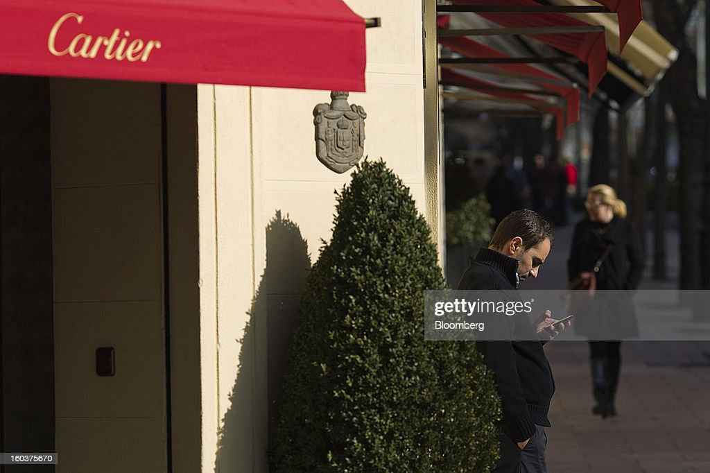 A pedestrian checks his mobile phone outside a Cartier luxury store, operated by Cie. Financiere Richemont SA, in Madrid, Spain, on Wednesday, Jan. 30, 2013. Spain's recession deepened more than economists forecast in the fourth quarter as the government's struggle to rein in the euro region's second-largest budget deficit weighed on domestic demand. Photographer: Angel Navarrete/Bloomberg via Getty Images