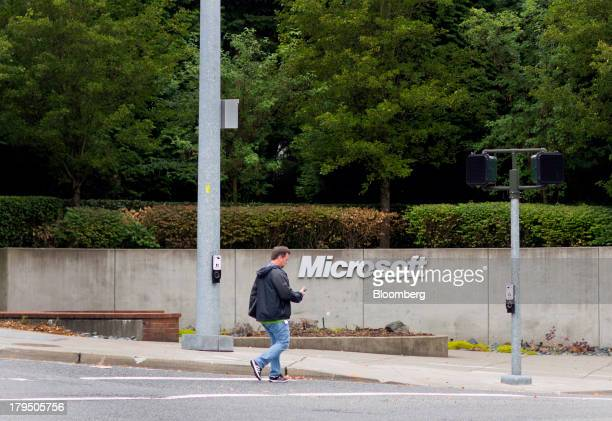 A pedestrian checks his mobile phone while crossing the street next to signage displayed at the Microsoft Corp campus in Redmond Washington US on...
