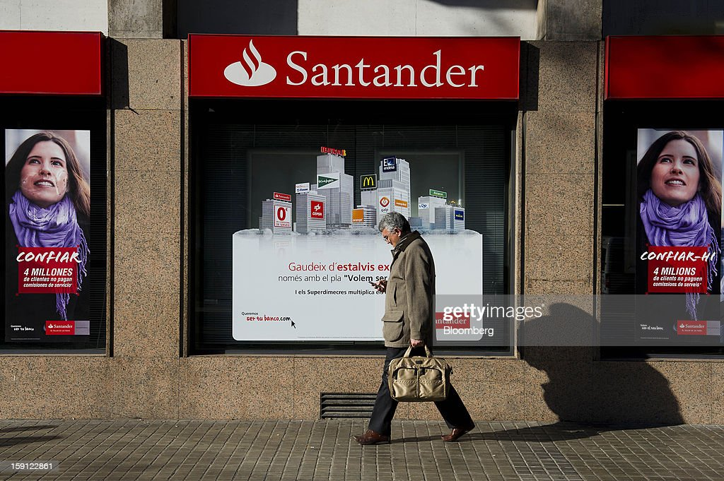 A pedestrian checks his mobile phone while passing advertisements in the windows of a Banco Santander SA bank branch in Barcelona, Spain, on Tuesday, Jan. 8, 2013. Banco Santander SA, Spain's biggest lender, will offer 263 million euros ($345 million) in stock to buy out minority investors in its Banco Espanol de Credito SA retail unit and close 700 local branches to cut costs. Photographer: David Ramos/Bloomberg via Getty Images