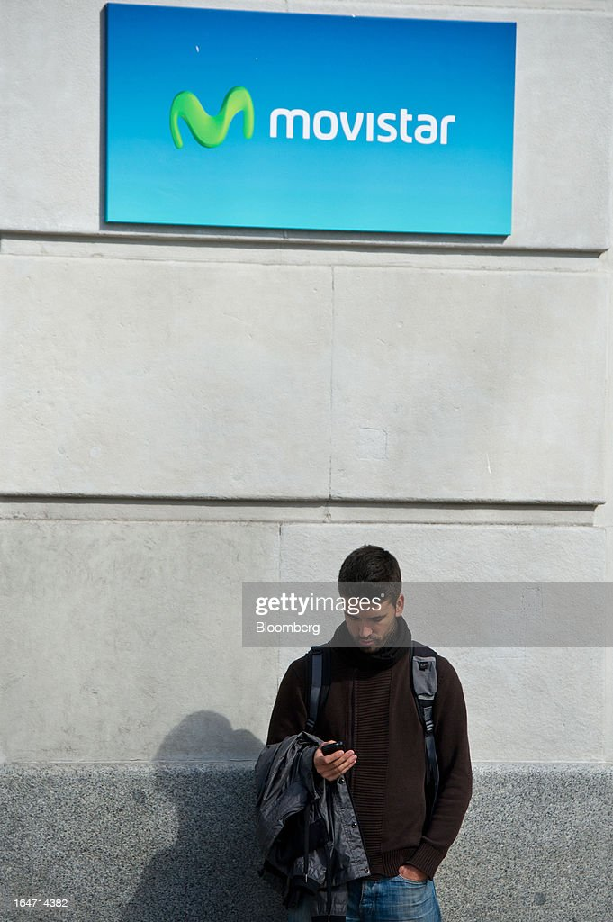 A pedestrian checks his mobile phone while standing beneath a Movistar logo displayed outside the Mobile World Centre building in Barcelona, Spain, on Tuesday, March 26, 2013. Telefonica, seeking to reduce net debt by more than 4 billion euros this year, is following companies such as Repsol SA, Spain's biggest oil company, and builder Actividades de Construccion & Servicios SA, to sell treasury shares. Photographer: David Ramos/Bloomberg via Getty Images