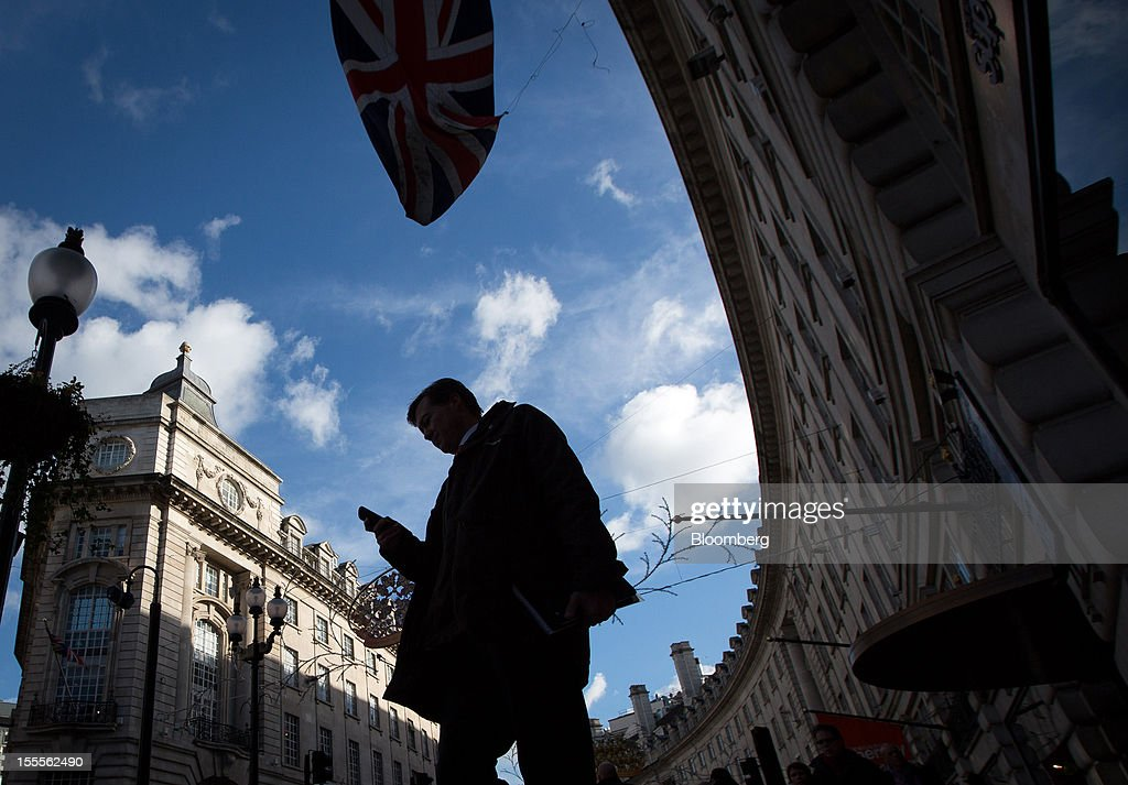 A pedestrian checks his mobile phone while walking along Regent Street in central London, U.K., on Monday, Nov. 5, 2012. Britain exited a double-dip recession in the third quarter with the strongest growth in five years as Olympic ticket sales and a surge in services helped boost the rebound. Photographer: Jason Alden/Bloomberg via Getty Images
