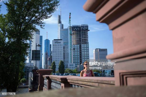 A pedestrian crosses a bridge on the River Main as skyscrapers stand beyond in Frankfurt Germany on Thursday July 20 2017 Frankfurt has emerged as a...