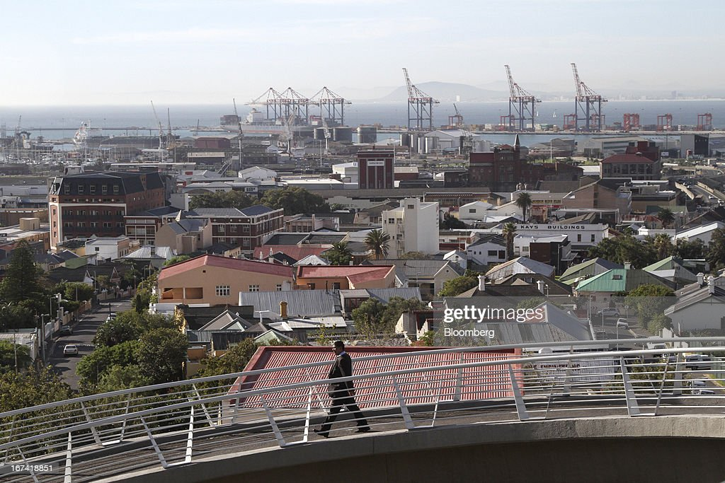A pedestrian crosses a bridge towards the Woodstock residential district near the harbour area in Cape Town, South Africa, on Wednesday, April 24, 2013. South Africa's gross domestic product is forecast to expand 2.6 percent this year, compared with 2.5 percent in 2012, according to the country's central bank. Photographer: Nadine Hutton/Bloomberg via Getty Images