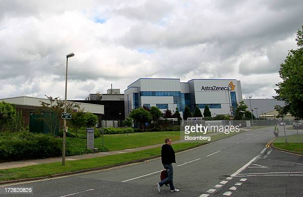A pedestrian crosses a road near AstraZeneca Plc's factory in Macclesfield UK on Thursday July 4 2013 AstraZeneca recently announced it will cut...