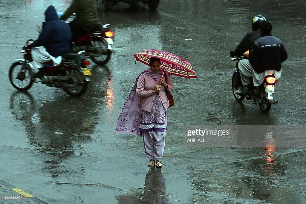 A pedestrian crosses a street during rain in Lahore on January 18, 2013. The Pakistan Meteorological Department (PMD) on Thursday forecast rain with snowfall over the hills at scattered places of province Punjab including Islamabad. AFP PHOTO/Arif ALI