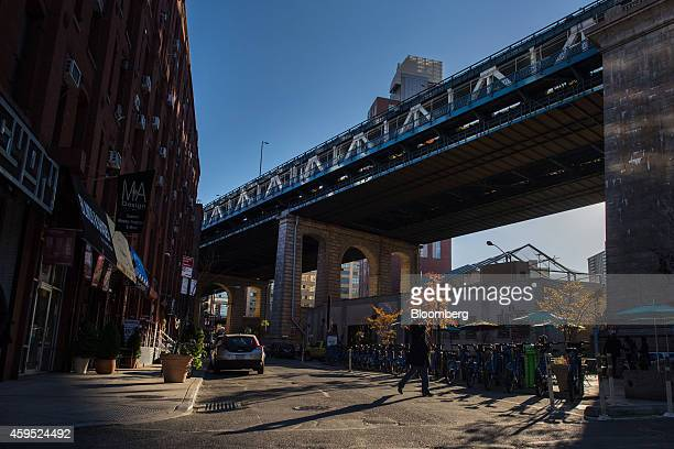 A pedestrian crosses Pearl Street in the DUMBO neighborhood in the Brooklyn borough of New York US on Saturday Nov 15 2014 DUMBO an acronym for Down...