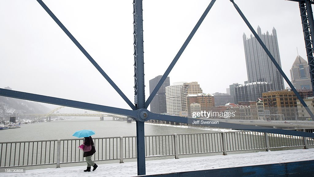 A pedestrian crosses the Smithfiled Street Bridge a winter storm blanketed the Midwest with snow December 26, 2012 in Pittsburgh, Pennsylvania. The storm has moved west from the Sierra Nevada across the Midwest and will head to the East Coast today.
