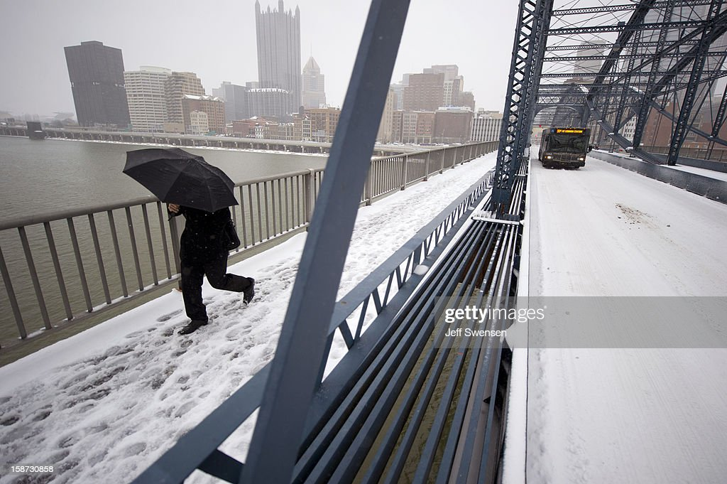 A pedestrian crosses the Smithfiled Street Bridge after a winter storm blanketed the Midwest with snow December 26, 2012 in Pittsburgh, Pennsylvania. The storm has moved west from the Sierra Nevada across the Midwest and will head to the East Coast today.