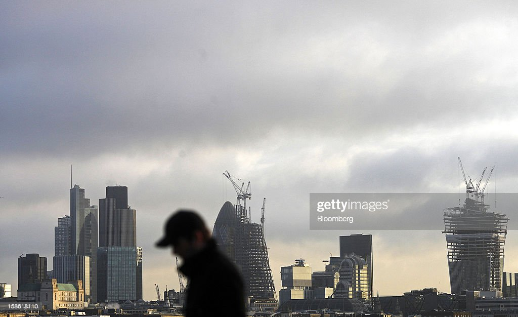 A pedestrian crosses Waterloo bridge against the skyline of the city of London, U.K., on Friday, Dec. 21, 2012. Britain's economy expanded less than previously estimated in the third quarter and the budget deficit unexpectedly widened in November, complicating Prime Minister David Cameron's attempts to bolster the recovery. Photographer: Simon Dawson/Bloomberg via Getty Images