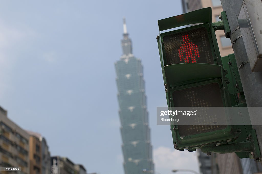 A pedestrian crossing light signals red at an intersection in front of the Taipei 101 building on Hsin Yi Road in Taipei, Taiwan, on Wednesday, July 24, 2013. Taiwan President Ma Ying-jeou ruled out driving down the Taiwan dollar to boost exports following the currencys rally against the yen and said the government still aims for growth of at least 2 percent this year. Photographer: Jerome Favre/Bloomberg via Getty Images