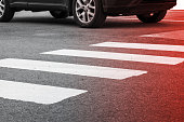 Pedestrian crossing road marking and moving car, photo with red gradient tonal filter, selective focus and shallow DOF