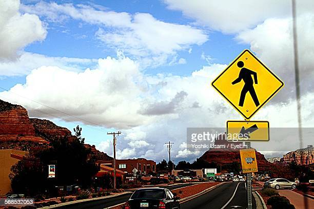 Pedestrian Crossing Sign Post By Road Against Cloudy Sky