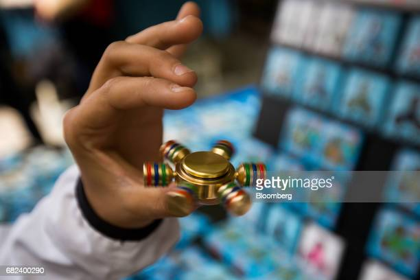 A pedestrian demonstrates a fidget spinner at a street vendor stand in New York US on Friday May 12 2017 The fidget spinner is a toy that sits like a...