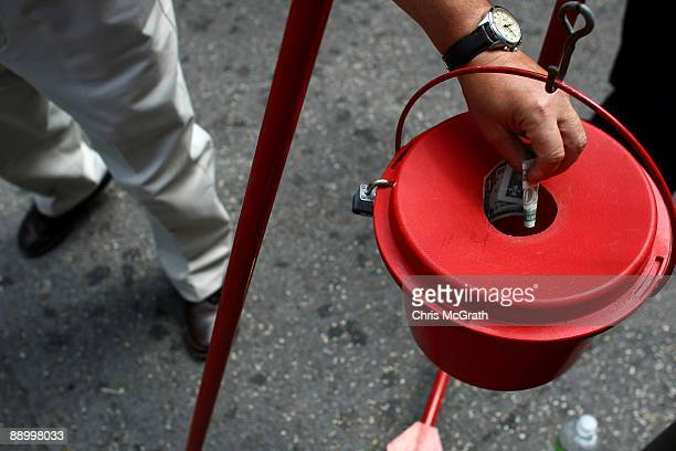 A pedestrian donates a dollar to the Salvation Army bellringer stand outside New York's Grand Central Station as part of an emergency fundraising...