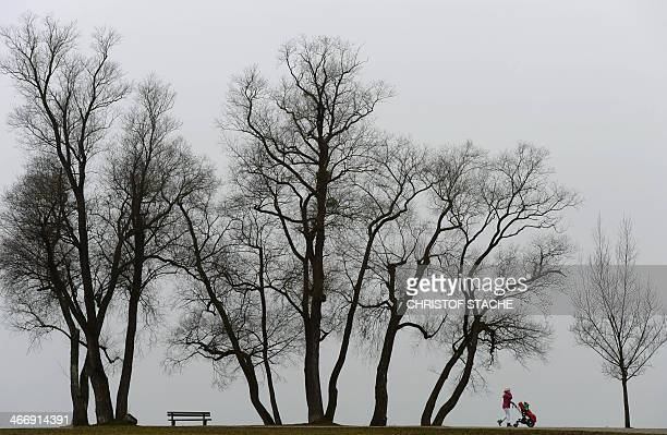A pedestrian enjoys a walk in front of trees near the lake Ammersee in Herrsching southern Germany during foggy winter weather and temperatures by...