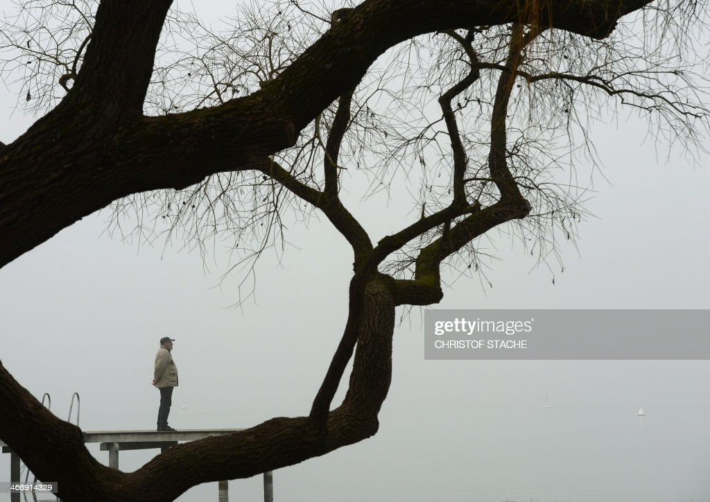 A pedestrian enjoys his walk at a rack near the lake Ammersee in Herrsching, southern Germany, during foggy winter weather and temperatures by the freezing point on February 5, 2014. Meteorologists forecast changeable weather during the week. AFP PHOTO/CHRISTOF STACHE
