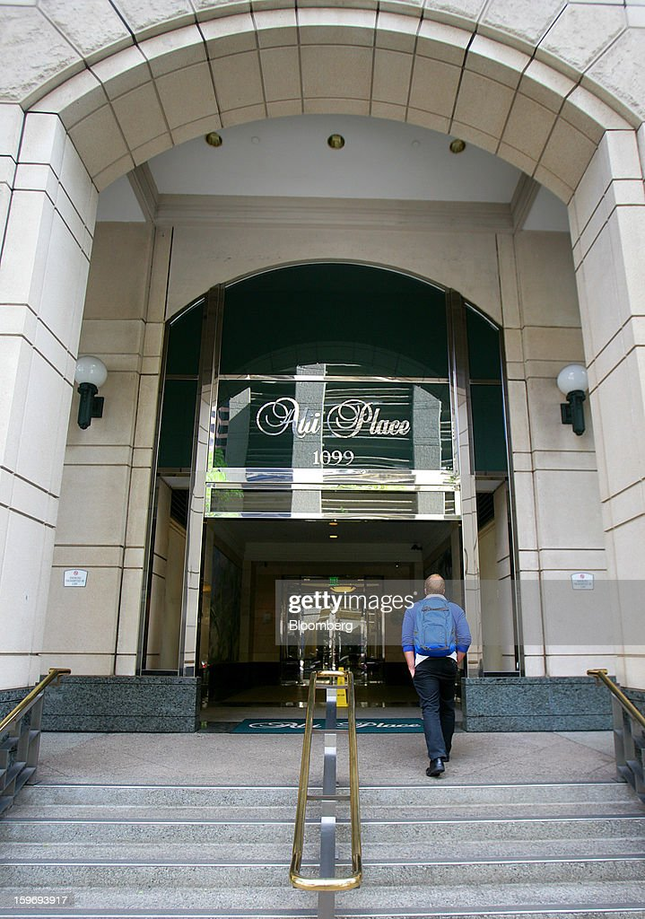 A pedestrian enters The Queen's Health Systems building in Honolulu, Hawaii, U.S., on Wednesday, Jan. 9, 2013. Honolulu, the southernmost major U.S. city, is a major financial center of the islands of the Pacific Ocean. Photographer: Tim Rue/Bloomberg via Getty Images