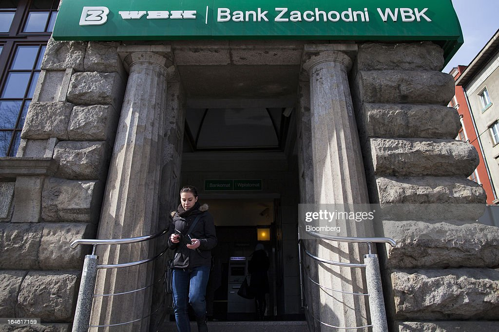 A pedestrian exits a Bank Zachodni WBK SA branch in Wroclaw, Poland, on Monday, March 25, 2013. KBC Groep NV of Belgium and Banco Santander SA of Spain raised 4.89 billion zloty ($1.51 billion) from the sale of a stake in Bank Zachodni WBK SA, Poland's third-largest lender. Photographer: Bartek Sadowski/Bloomberg via Getty Images
