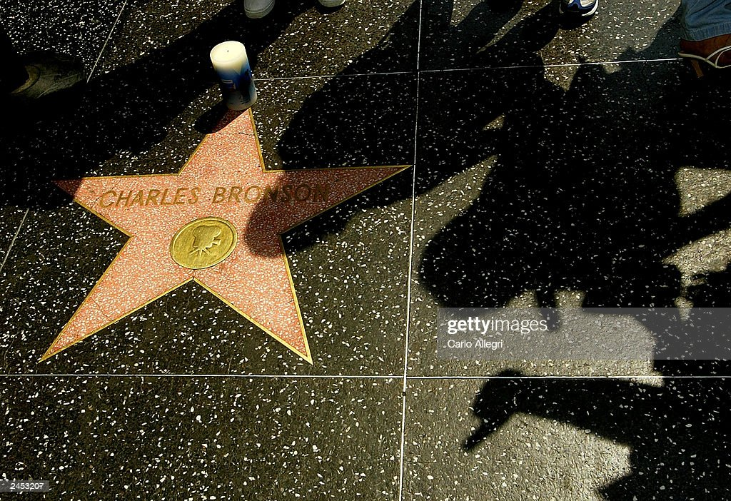 A pedestrian gives a thumbs-up as he passes the star of actor Charles Bronson on the Hollywood Walk of Fame September 1, 2003 in Hollywood, California. Bronson died of pneumonia at the age of 81 August 30, 2003 in Los Angeles, California.