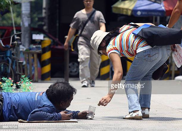 A pedestrian gives alms to a beggar along a street in Manila on July 7 2009 Five million of the Philippines poorest families will receive cash or...