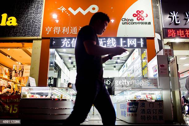 A pedestrian holding a mobile phone walks past signage for China Unicom Ltd at a store in the Gongbei district of Zhuhai Guangdong province China on...