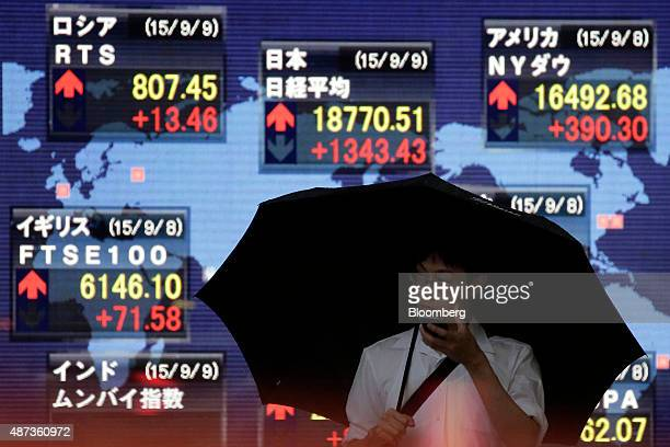 A pedestrian holding an umbrella holds a mobile device in front of an electronic stock board displaying the closing figure of the Nikkei 225 Stock...